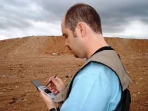 Minas inspector with palmtop at landfill site